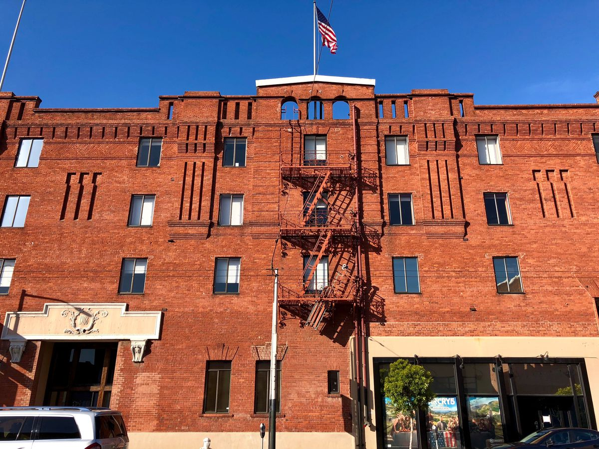 The exterior of 625 Third in San Francisco. The facade is red brick. There is a United States flag on the roof.