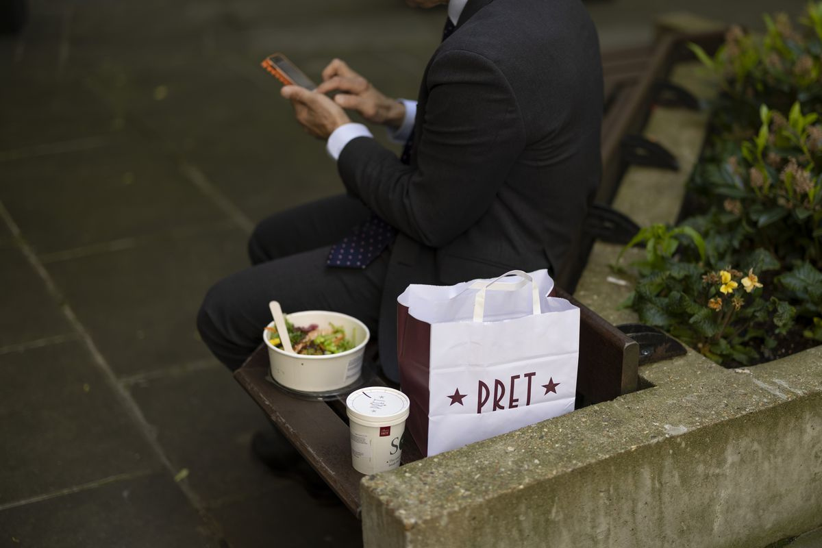 A Pret a Manger takeaway bag, coffee, and tub of salad on a stone bench, with an office worker in a suit sat next to them looking at their phone
