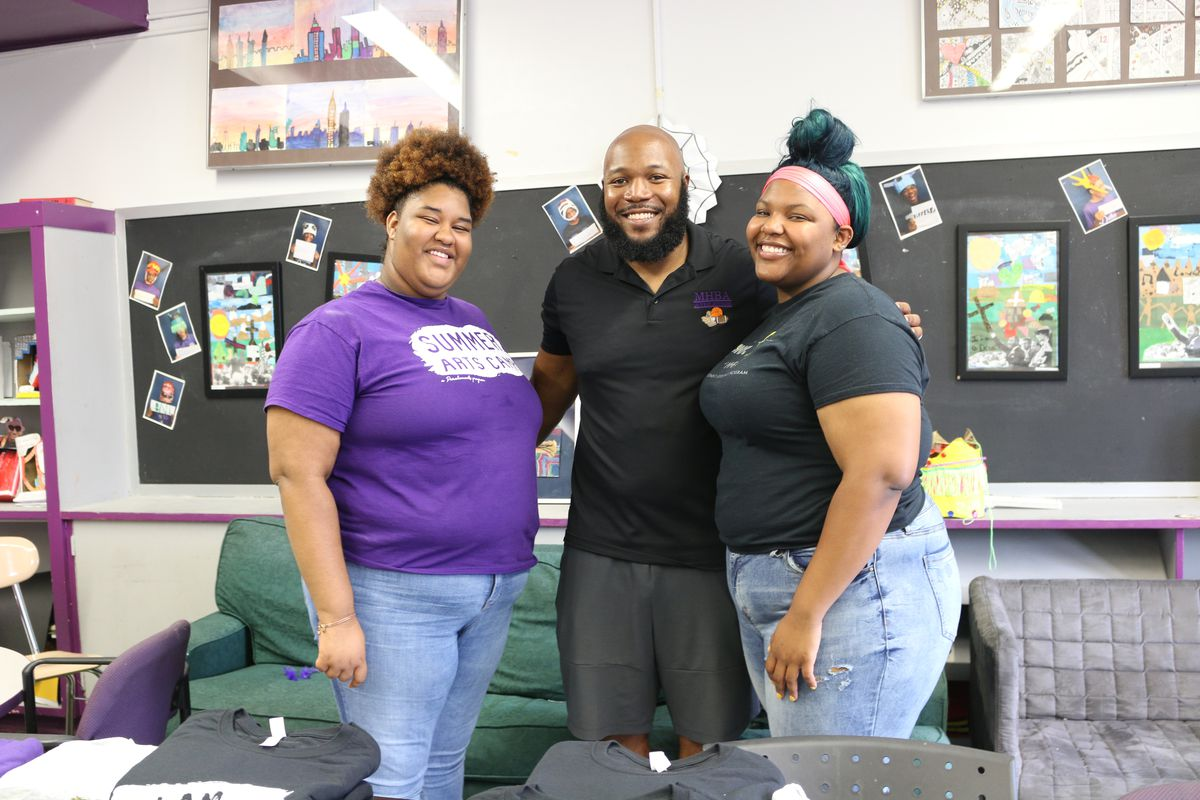 """The Mott Hall Bridges Academy guidance counselor, Wesley McLeod, center, with two former students, whom he helped counsel after the deaths of their parents. The Brownsville middle school has been praised for its """"grief-sensitive"""" approach to education."""
