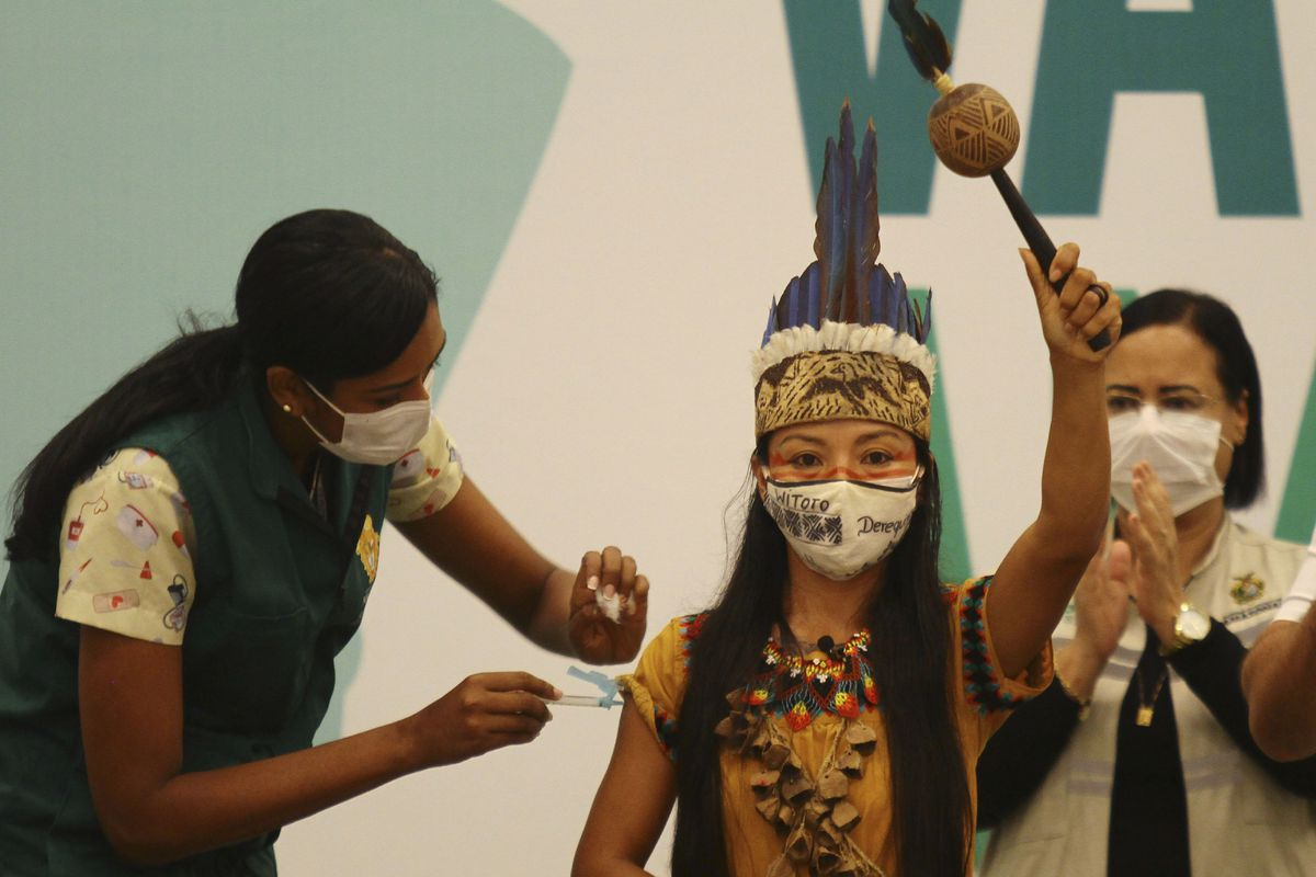 Health worker Vanda Ortega, from the Witoto Indigenous group and dressed in traditional clothing, is the first woman to receive the COVID-19 vaccine produced by China's Sinovac Biotech Ltd, during the start of the vaccination program in Manaus, Amazonas state, Brazil, Monday, Jan. 18, 2021.