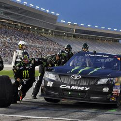 Crew members work to service Kyle Busch's car during a pit stop in the NASCAR Nationwide Series auto race at Atlanta Motor Speedway, Saturday, Sept. 1, 2012, in Hampton, Ga.