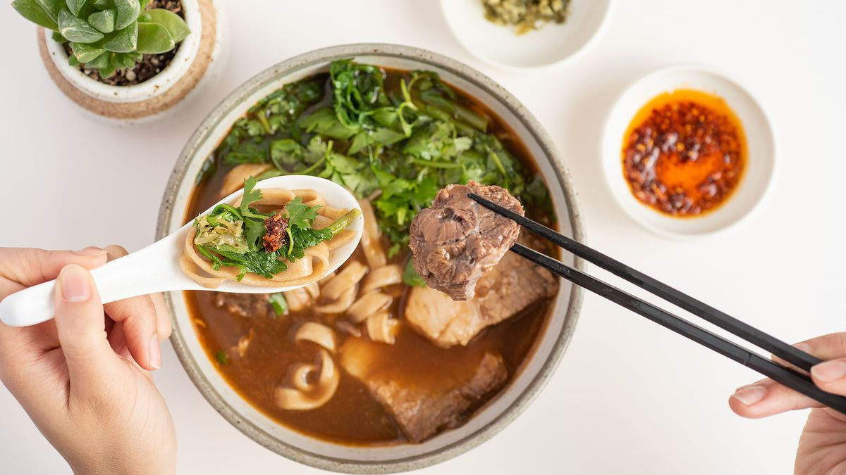 A bowl of beef noodle soup being eaten.