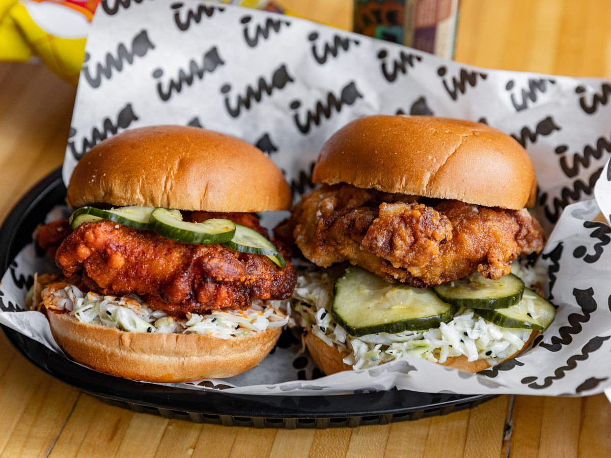 A hot chicken sandwich and a plain karaage chicken sandwich in a basket lined with Ima paper.