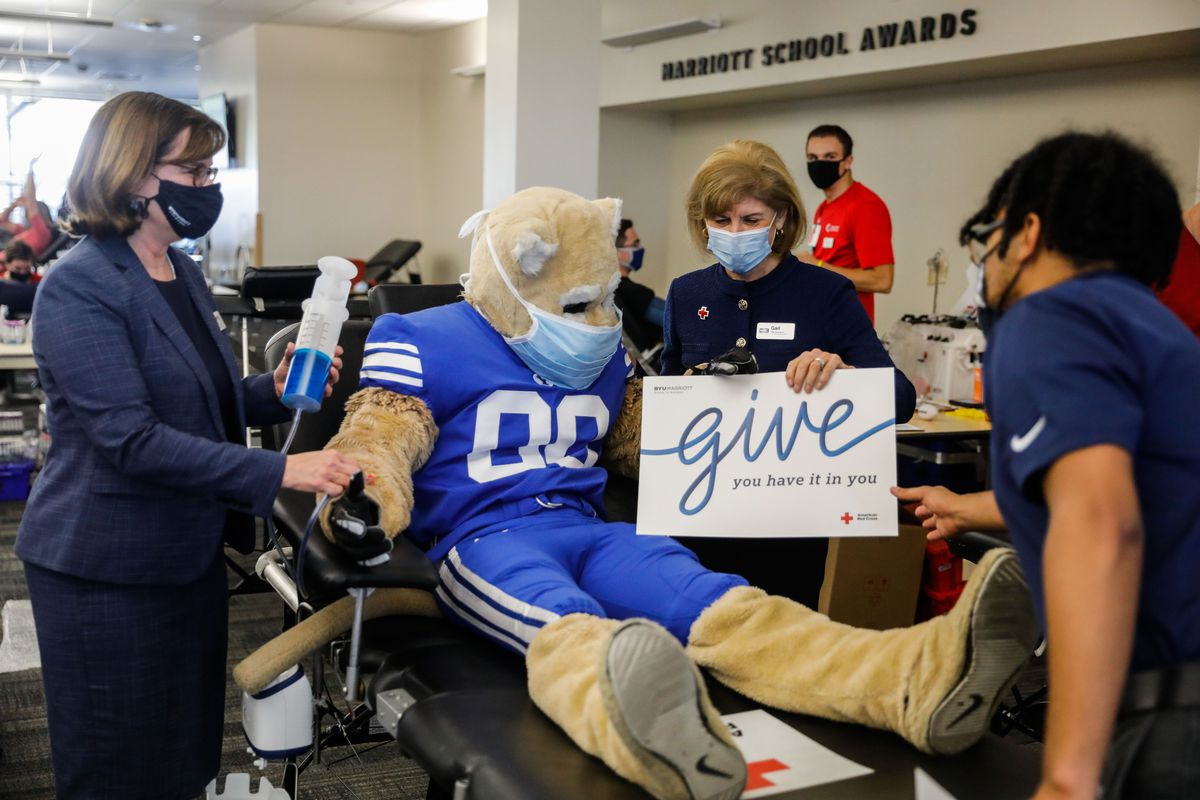American Red Cross president and CEO Gail McGovern prepare for a photo with BYU mascot Cosmo the Cougar at a blood drive.