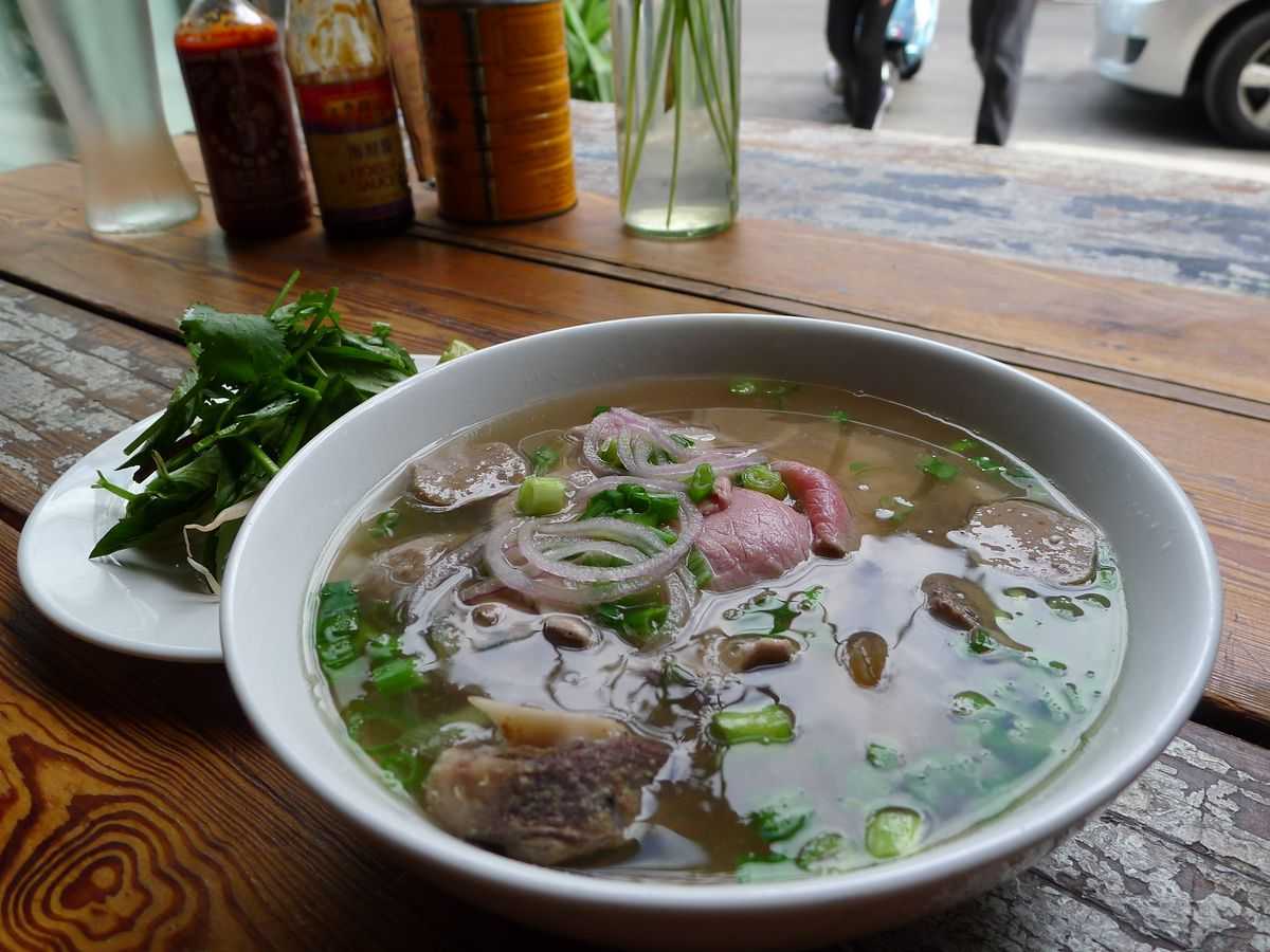 A bowl of pho with a handle seen in the open window of the restaurant.