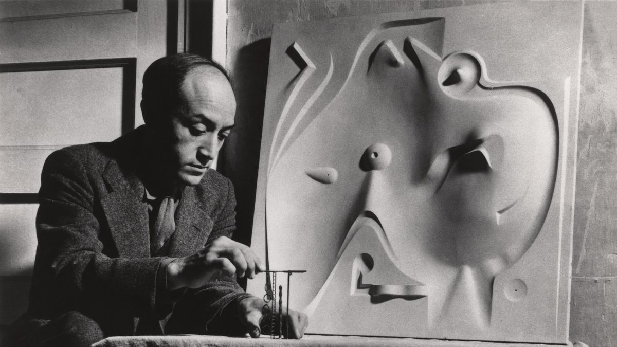 A man sits in front of a bas-relief plaster sculpture of an undulating playscape while looking at tiny versions of abstract structures