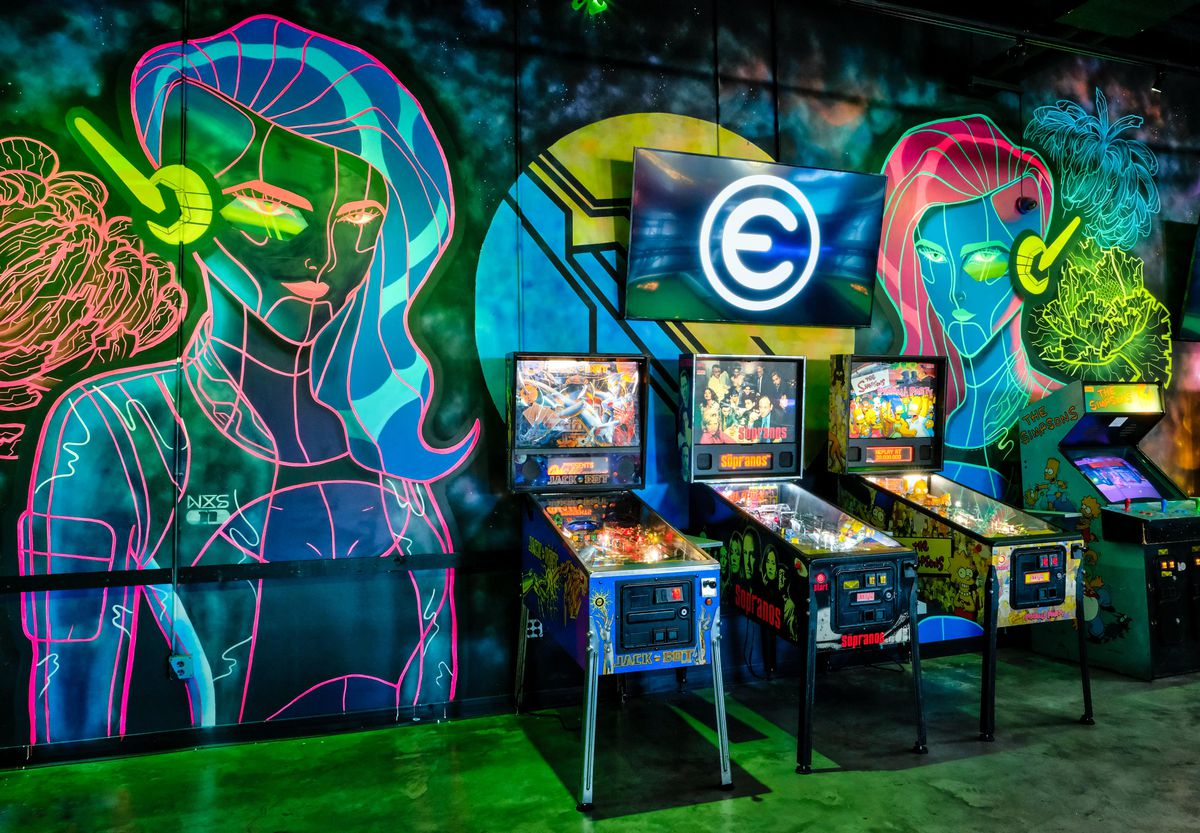 Three pinball machines in front of a graffiti wall