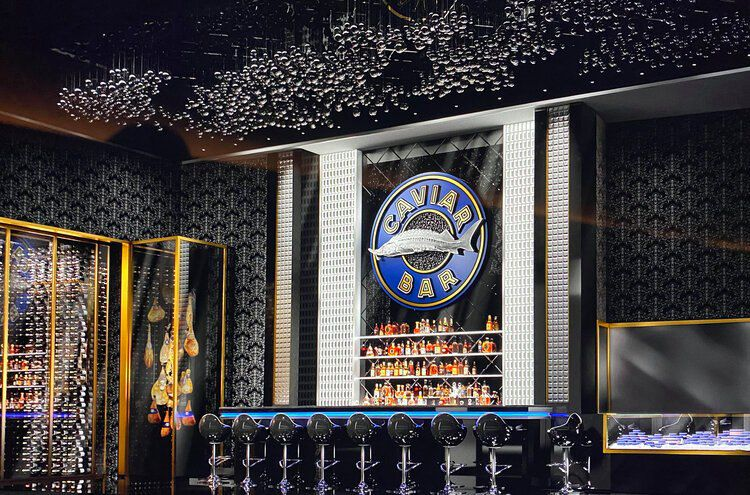 A dark bar with a sturgeon logo behind it and stools with blue seats,