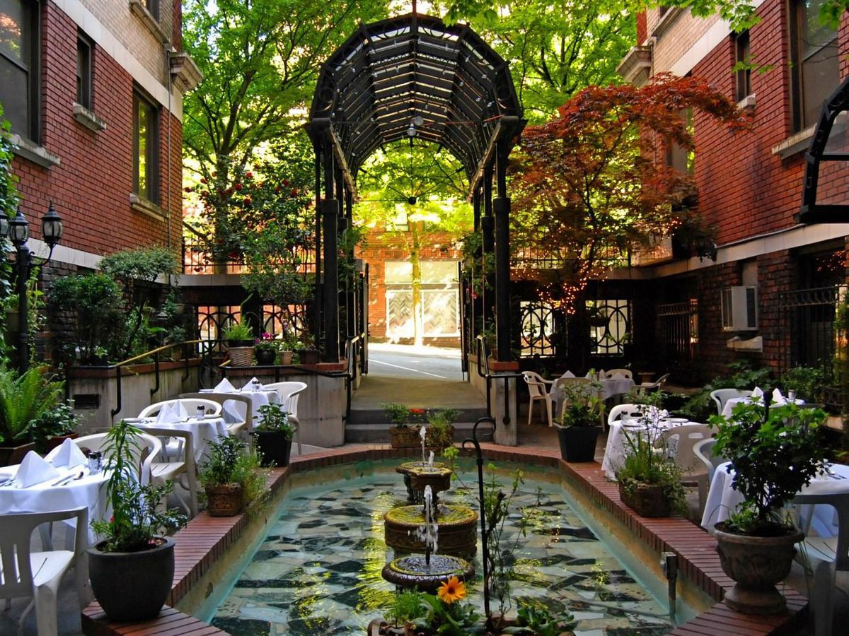 The outdoor dining area at La Fontana Siciliana, with a fountain and a decorative entryway.
