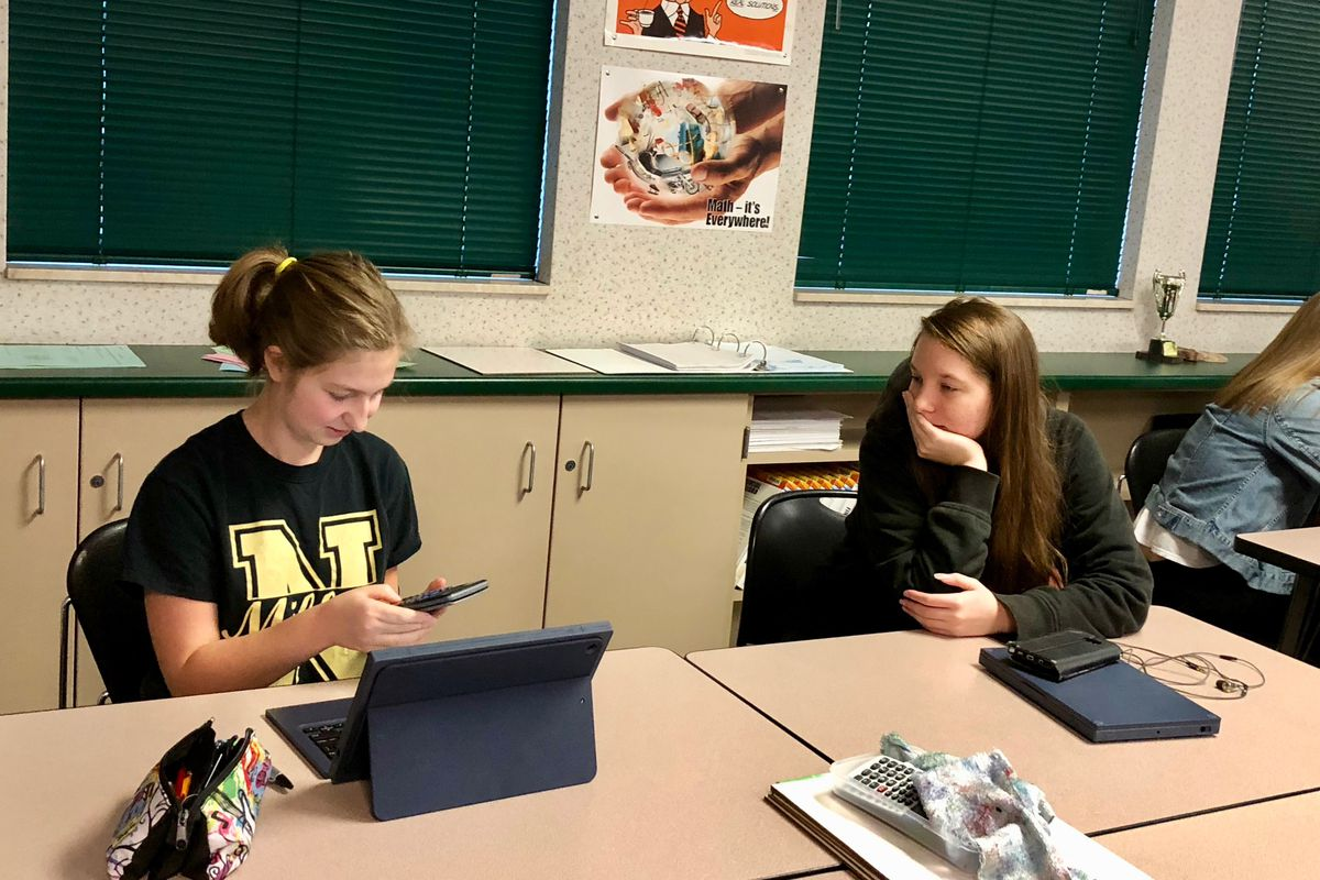 Two Noblesville High School students work through a project related to texting and driving for their financial Algebra 2 class.