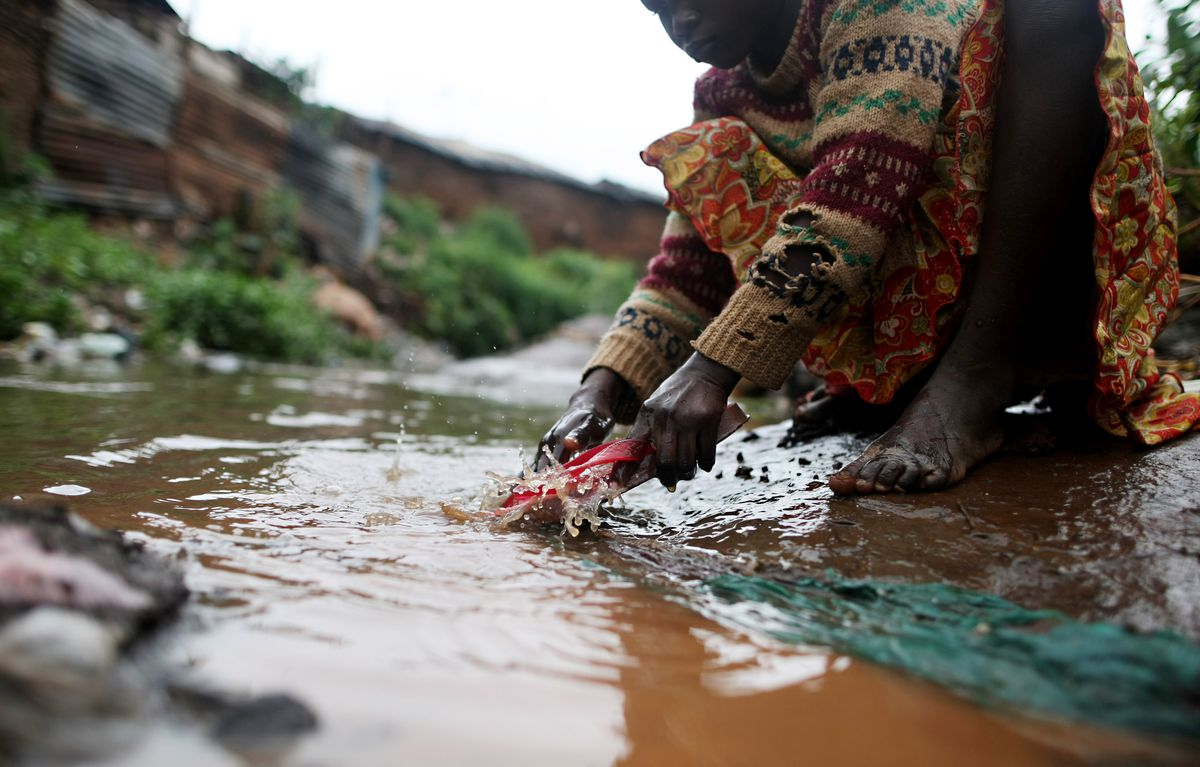 A girl washes her muddy sandals on a polluted water canal in Kibera, in 2010.
