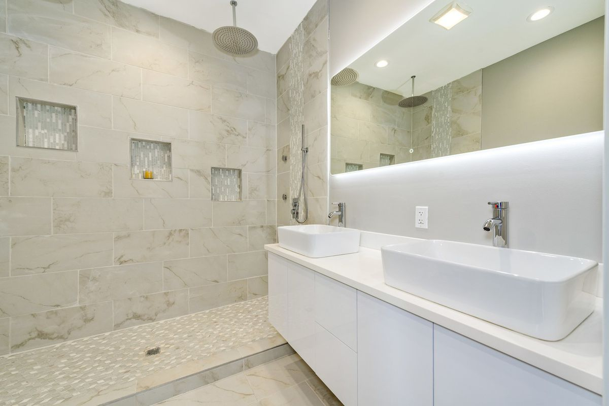 A large walk-in shower with tiled walls next to a sleek white vanity with twin bowl sinks and a floating backlit mirror.