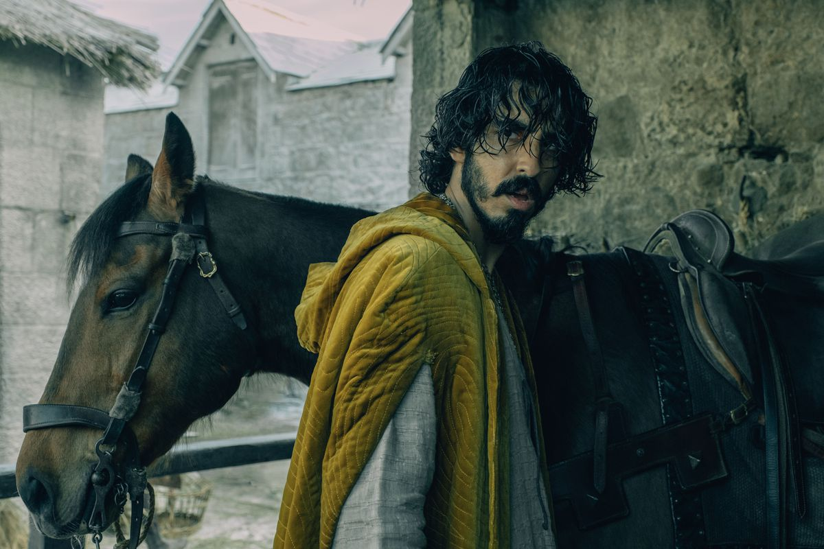 Dev Patel, looking grimy as hell in front of a horse in David Lowery's The Green Knight