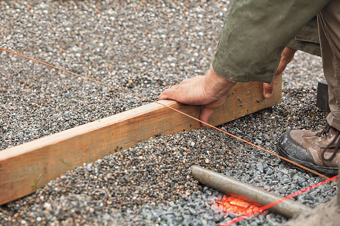Man Uses Screed Board Over Pipes To Set Permeable Pavers
