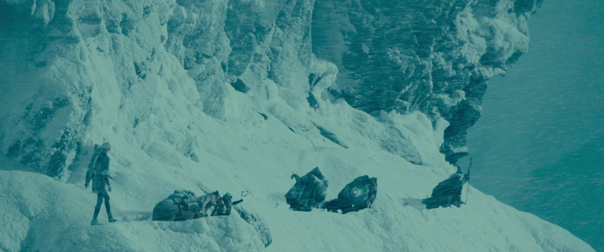 The Fellowship trudges through deep snow on a mountainside as Legolas steps sprightly on top of it in The Fellowship of the Ring.