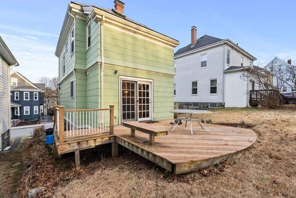 The back of a two-story house with a crescent-shaped new deck off it.