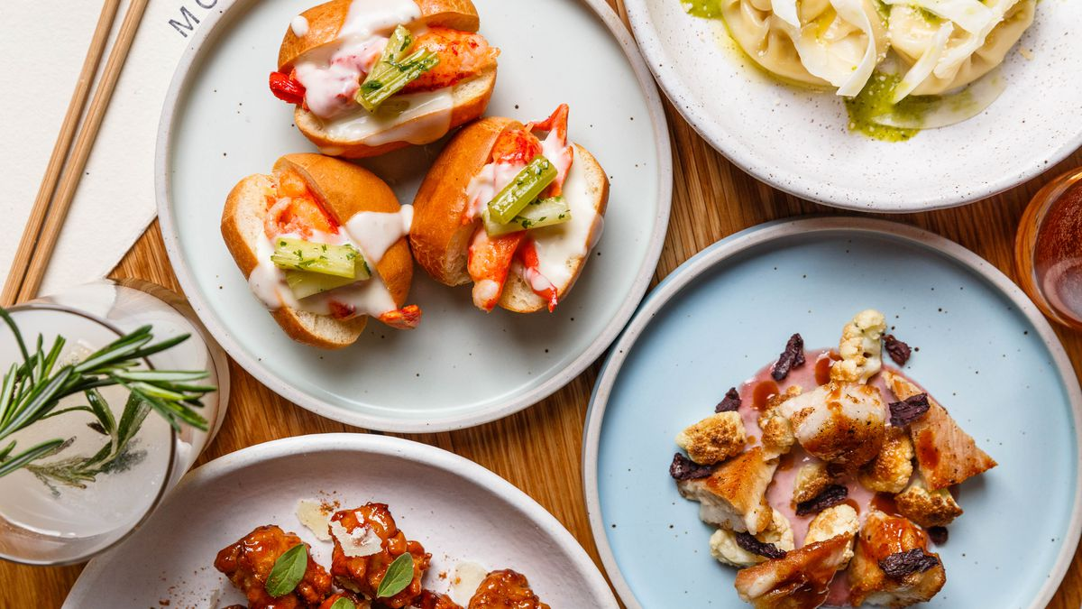 A spread of food on ceramic plates, including tiny lobster rolls, pork jowl, and corn dumplings.