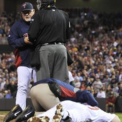 Minnesota Twins manager Ron Gardenhire, left, is held up momentarily by plate umpire Gary Cederstrom after Twins' Chris Parmelee went down as he was hit in the helmet by a pitch from Boston Red Sox's Justin Thomas in the sixth inning of a baseball game Wednesday, April 25, 2012, in Minneapolis. Parmelee left the game.
