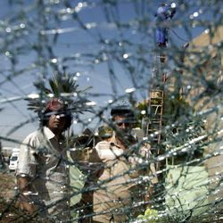 Iraqis are seen through a shattered windshield of a vehilce at the scene of a car bomb attack in Baghdad, Iraq, Sunday, Sept 30, 2012. A rapid-fire series of explosions in Baghdad while Iraqis were going to work on Sunday morning, killed and wounded scores of people, police said.