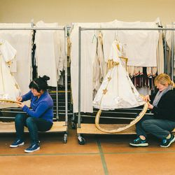 Two seamstresses work on the children's angel costumes.