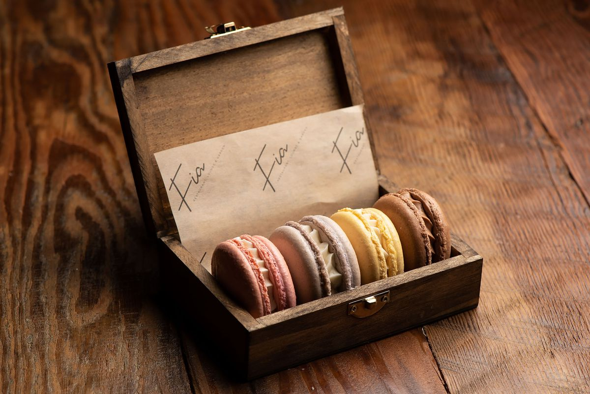 Macarons filled with icing sitting in an older wooden box.