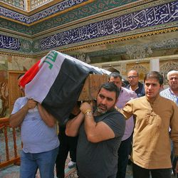 Mourners carry the Iraqi flag-draped coffin of, Talib Hassan, 35, who was killed of bomb in Karada neighborhood, during a funeral procession at the holy shrine of Imam Ali in Najaf, 100 miles (160 kilometers) south of Baghdad, Iraq, Sunday, July 3, 2016. Dozens of people have been killed and more than 100 wounded in two separate bomb attacks in the Iraqi capital Sunday morning, Iraqi officials said.