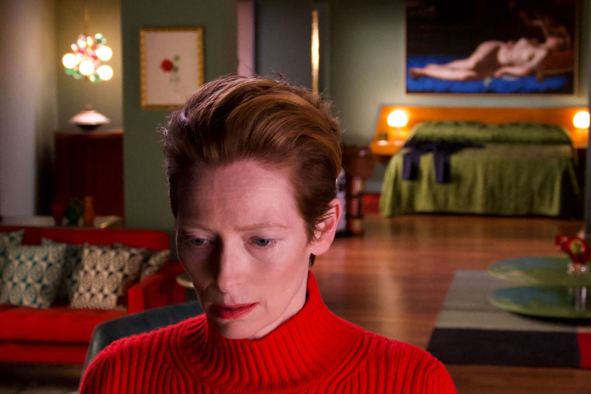Tilda Swinton in a richly-colored room, wearing a bright red turtleneck.