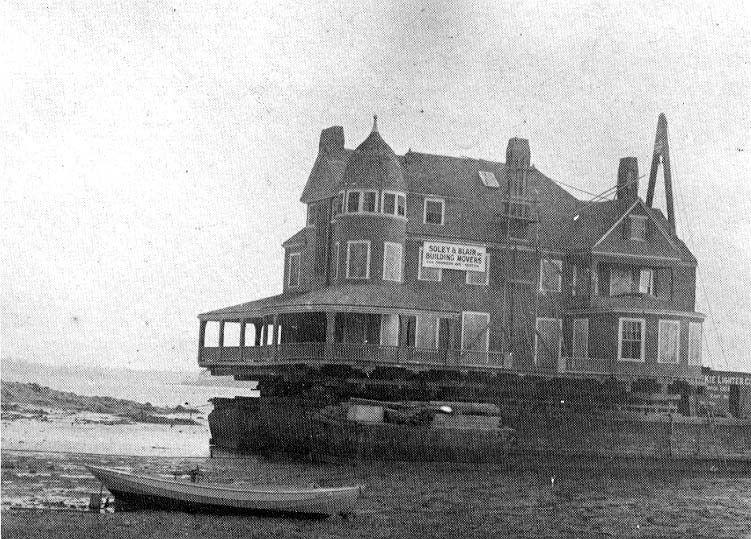 A multi-story house on a promontory on the coast.