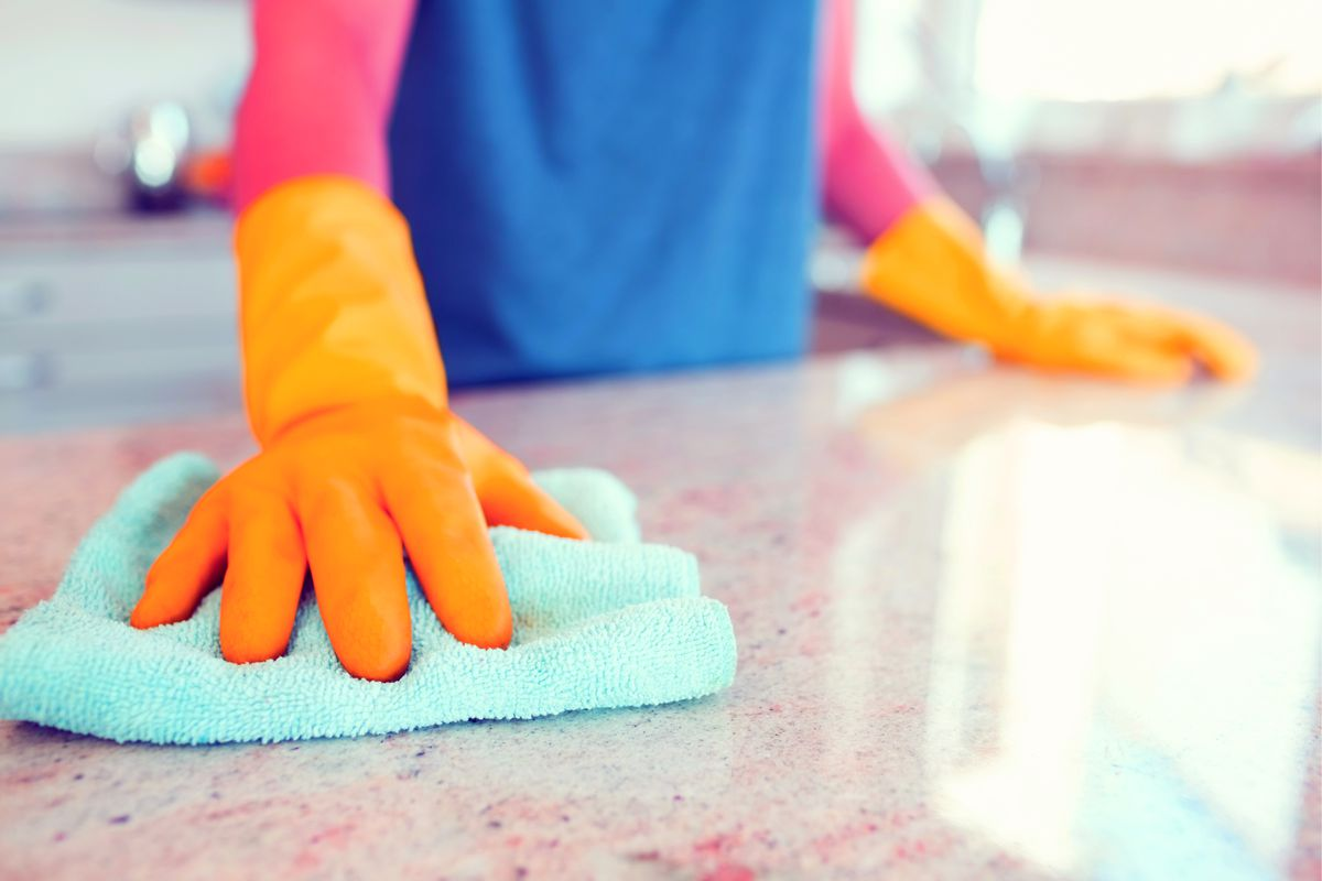 A pair of hands in kitchen gloves wipes down a counter.
