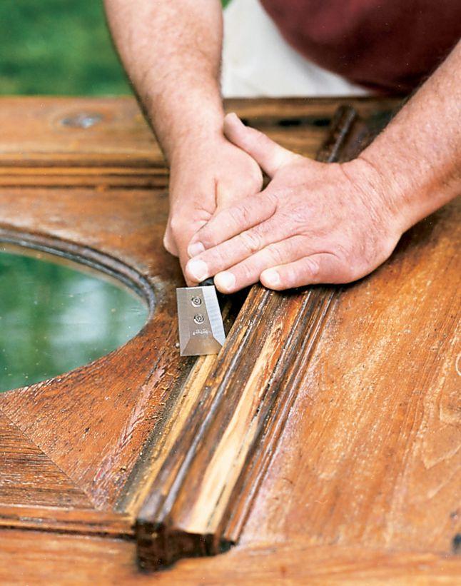 Man Uses Small Scrapers To Scrape Moldings Off Wood Door