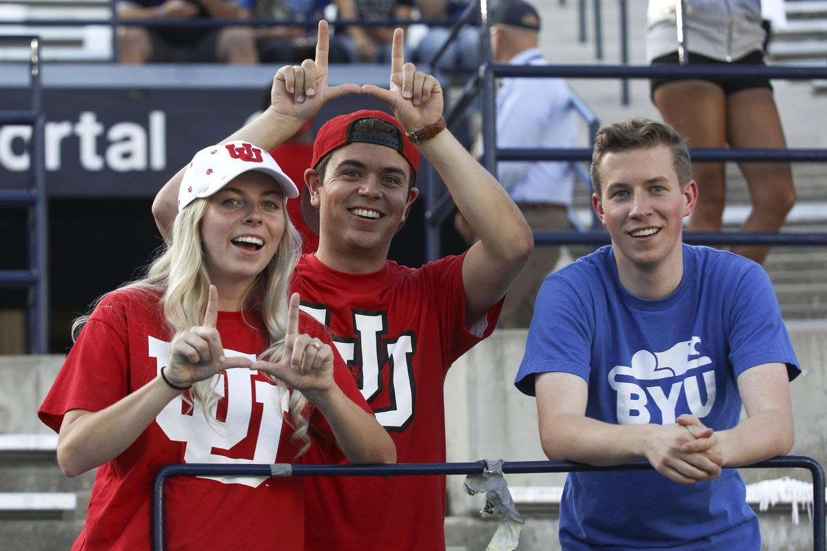 Utah fans Joseph Hallman, center, and his wife Jordan Wunderli, stand with Hallman's cousin, Ben Young, prior to the start of the University of Utah at BYU football game at LaVell Edwards Stadium in Provo on Thursday, Aug. 29, 2019.
