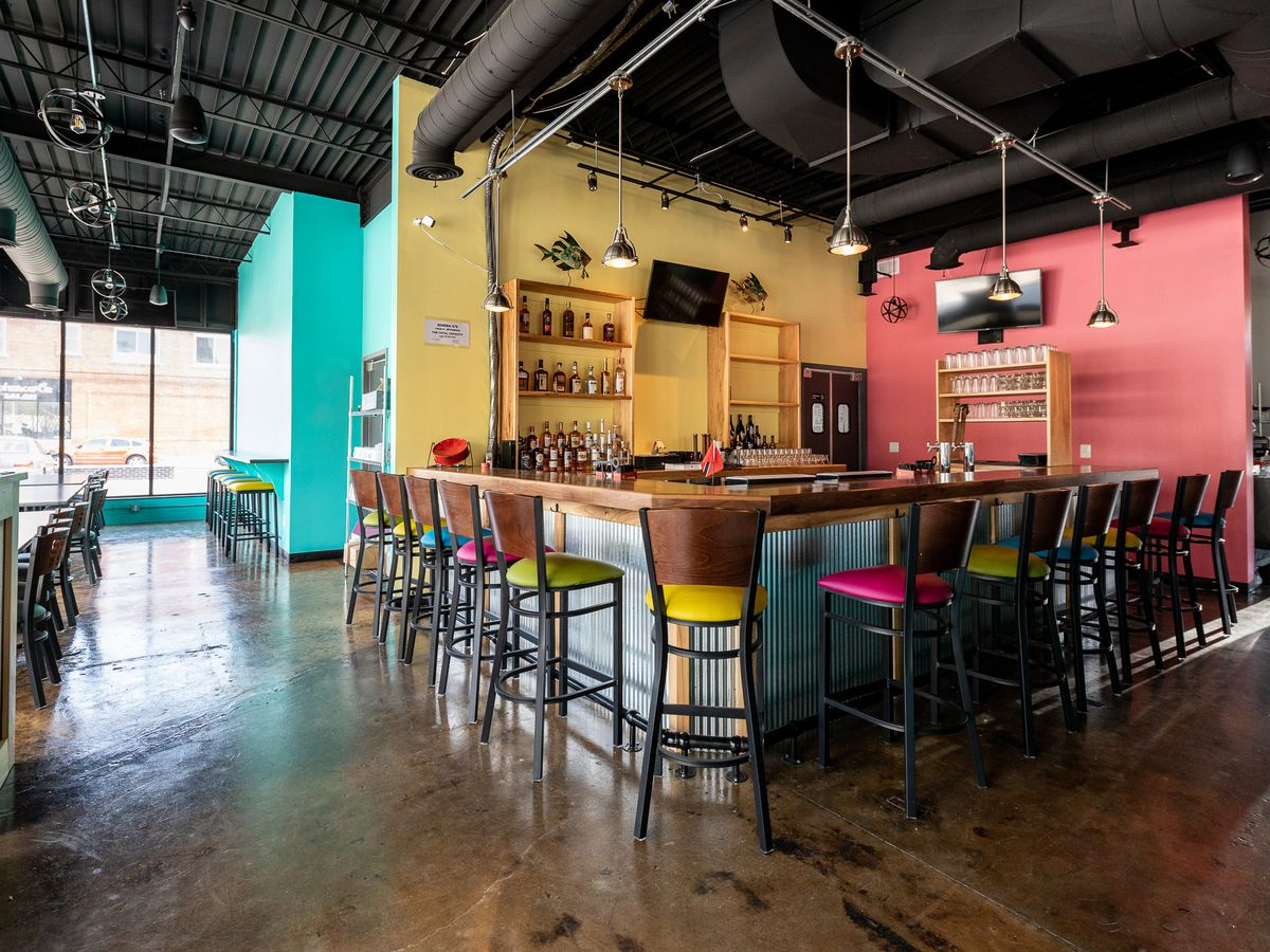 an empty restaurant with a square bar. the walls are painted aqua, yellow, and pink