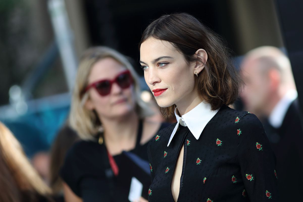 Alexa Chung wears navy dress with a pointy white collar on the red carpet.