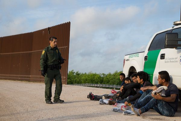 A Border Patrol agent apprehends illegal immigrants shortly after they crossed the border from Mexico into the United States on Monday, March 26, 2018 in the Rio Grande Valley Sector near McAllen, Texas.