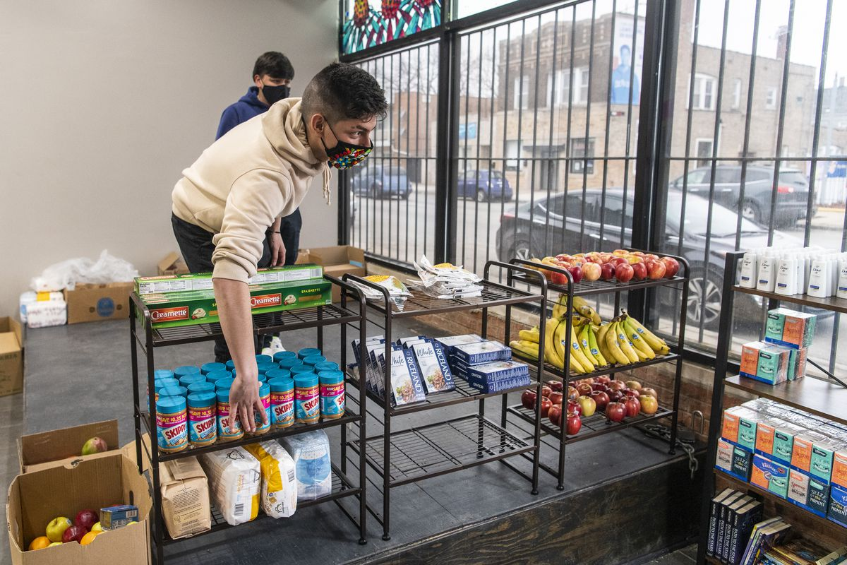 Diego Garcia restocks a food shelf for individuals in the community to come and take, at the Gage Park Latinx Council's Cultural Center, Wednesday, March 17, 2021.