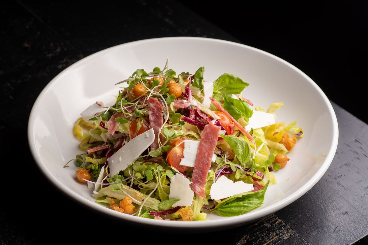 A large bowl of chopped salad with salami.