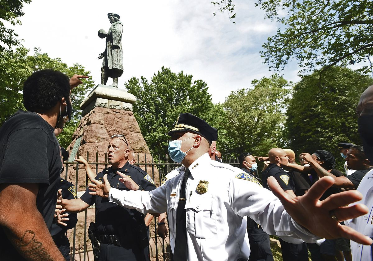A man at left points to the statue of Christopher Columbus as police hold the crowd back before the statue was removed from Wooster Square Park, in New Haven, Conn. Disputes over what to do with statues of Christopher Columbus in Connecticut have resulted in both civil and criminal complaints.