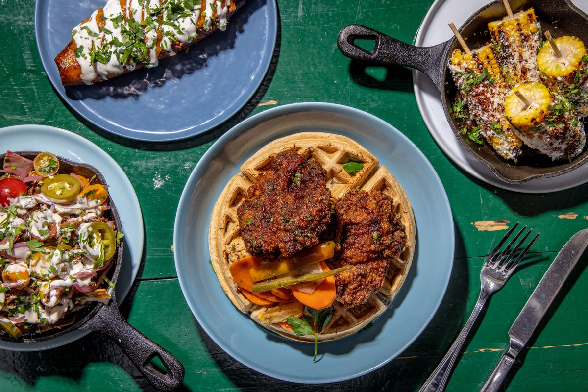 Golden sumac chicken over falafel waffles sits in the center of the photograph in an overhead shot; a variety of other dishes flank the chicken, including maduro mahshi, plantain nachos, and Mexican corn