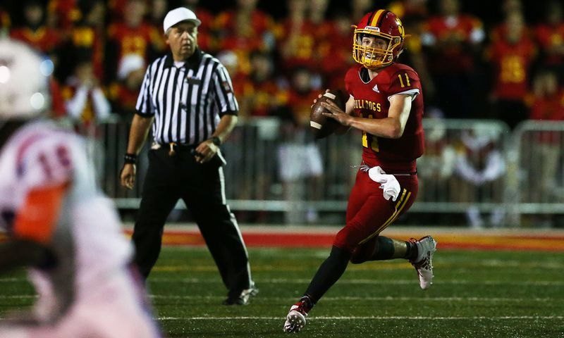 Batavia's Kyle Oroni (11) rolls out to throw a pass against East St. Louis.
