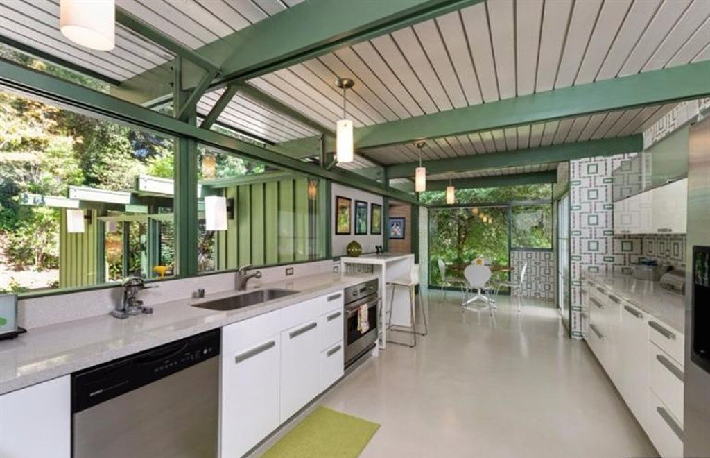 A midcentury modern kitchen with a white wooden ceiling that has green support beams. The cabinetry is white. There is white, green, and grey patterned wallpaper on the walls.
