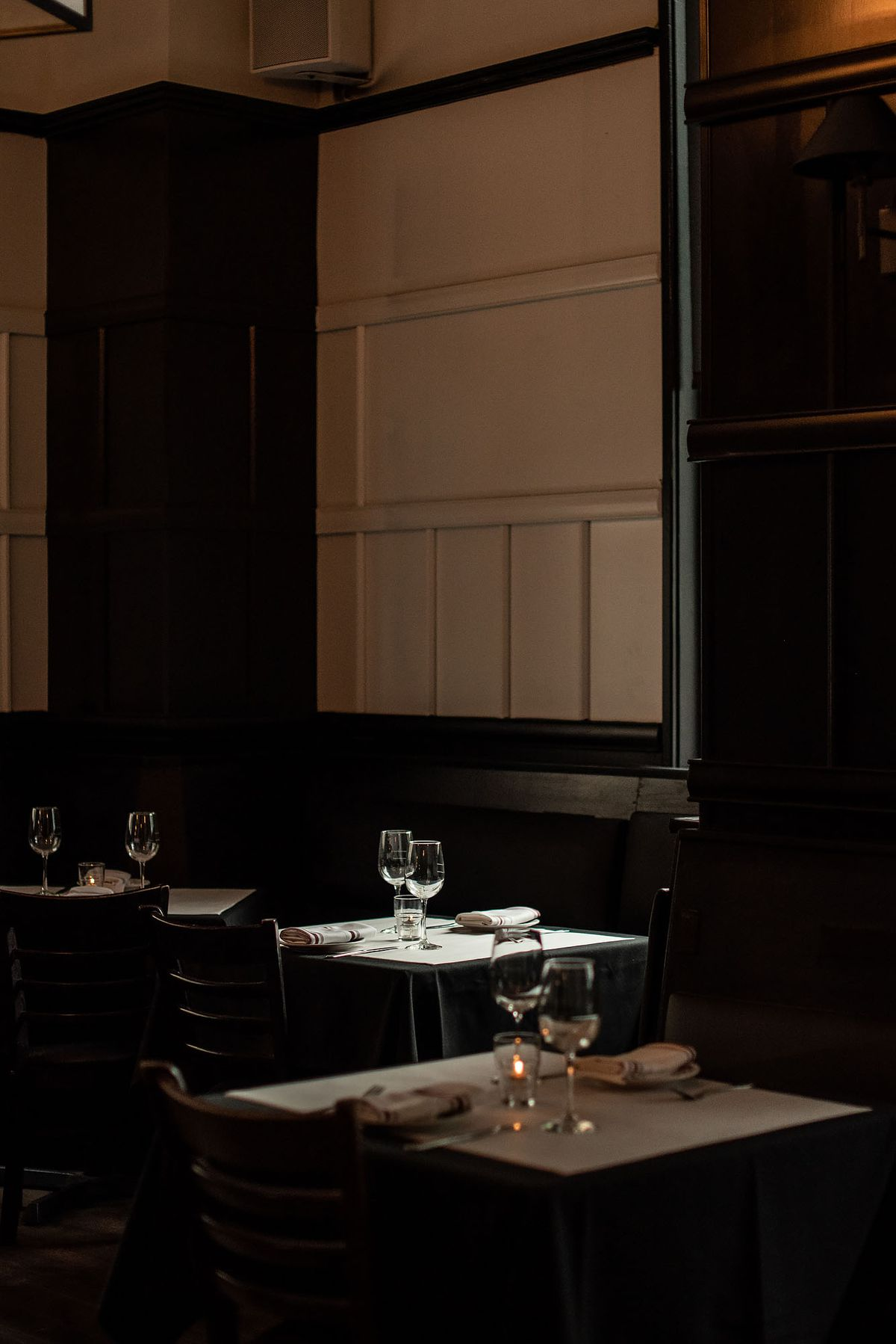 A pendant light glows over a single table inside a fine dining restaurant.