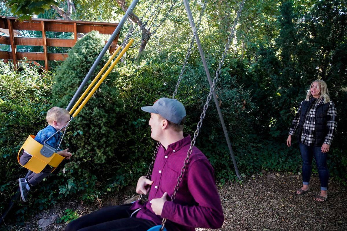 Haley Jeppson and her husband, Brookston, watch as son Sammy, 2, swings on a swingset at Jeppson's parents' house in Salt Lake City on Sunday, Oct. 3, 2021. The American Family Survey has tracked attitudes about marriage and family life since 2015.