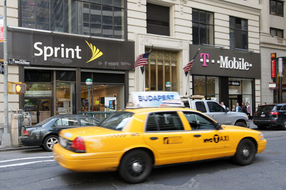 A taxi drives past a Sprint store next to a T-Mobile store