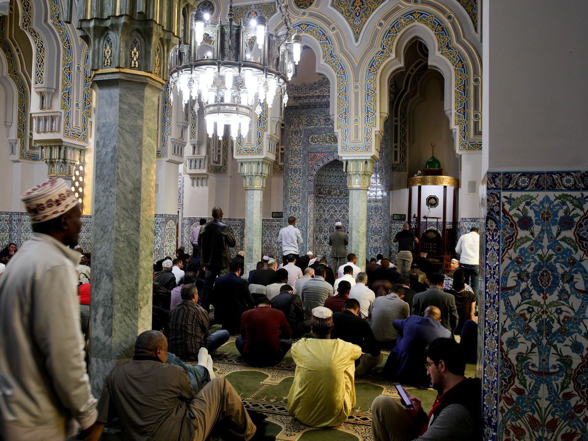 The inside of a mosque, filled with people. There are tiles throughout.