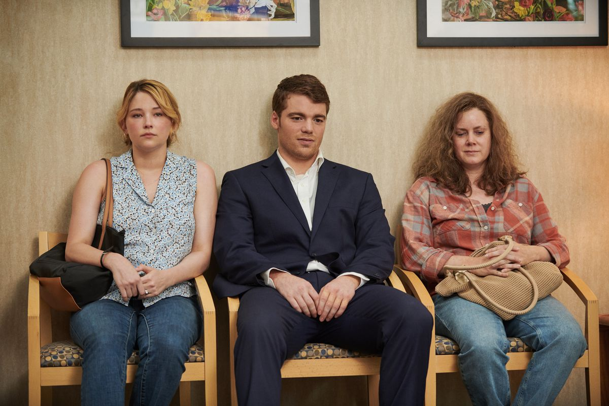 A two women and a man sit in a waiting room.