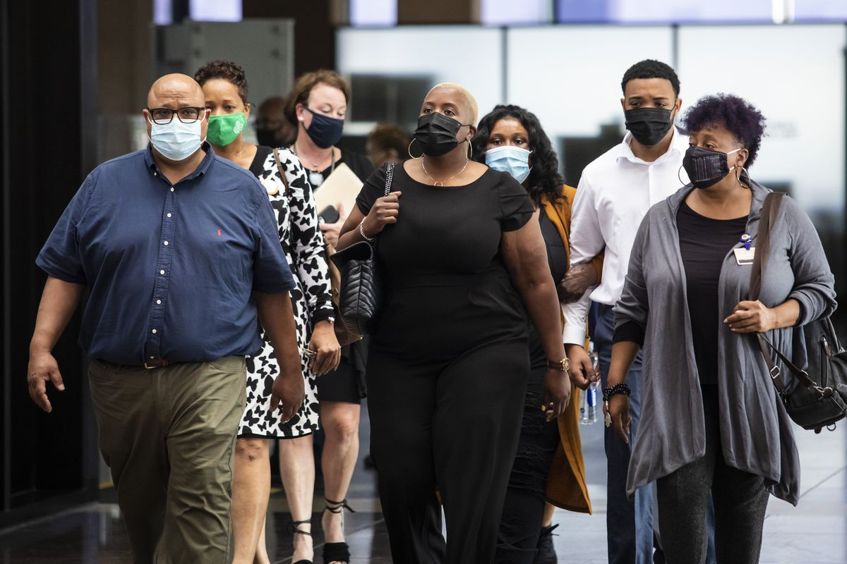 Hadiya Pendleton's parents, Cleopatra Cowley (center) and Nathaniel Pendleton Sr. (left), walk with supporters Tuesday afternoon into the Leighton Criminal Courthouse.