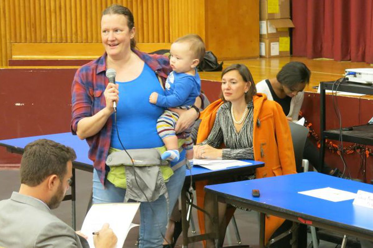 Carole-Ann Moench, a teacher at Global Neighborhood Secondary School, expresses her reluctant support for a plan to merge the school with P.S. 96. To the right is Deputy Chancellor of Operations Elizabeth Rose. ( Photo by Geoff Decker )