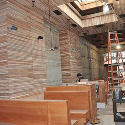 """Repurposed salvaged lath from the demolition includes """"coffee bag"""" wainscoting, Meyer speakers and microphones. A new central skylight was cut out.  In the background, glimpse the entry to the back patio."""