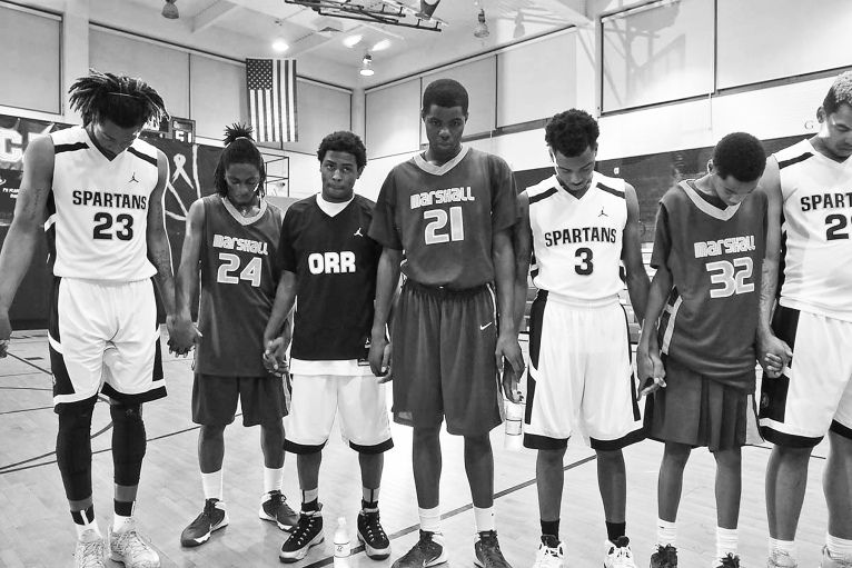 Players from Orr and Marshall say a prayer for assist Coach Shawn Harrington who was shot on his way to work.