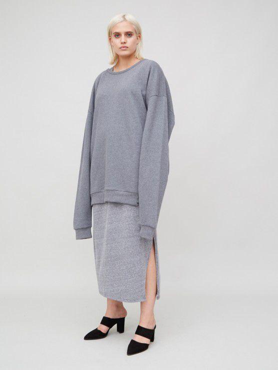 A model wears an oversized sweatshirt over a grey maxi dress